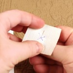 Pushing a pin through the center of the tape square